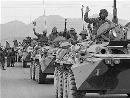A convoy of Soviet tanks wave to crowds after their arrival in Kabul from the eastern city of Jalalabad as part of the Soviet withdrawal from Afghanistan May 15, 1988.   REUTERS/Richard Ellis