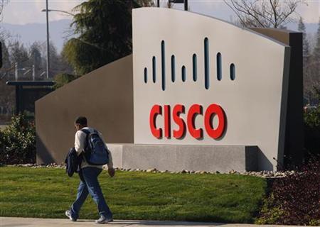 A pedestrian walks past the Cisco logo at the technology company's campus in San Jose, California February 3, 2010. REUTERS/Robert Galbraith/Files