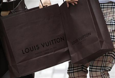Mainland Chinese visitors hold Louis Vuitton shopping bags outside a Louis Vuitton store at Hong Kong's Tsim Sha Tsui shopping district May 24, 2011. REUTERS/Tyrone Siu/Files