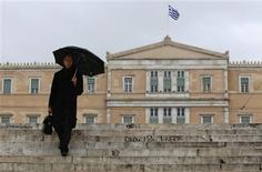 A man makes his way during a rainy day in front of the parliament in Athens February 16, 2012.  REUTERS/Yiorgos Karahalis