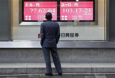 A man looks at a display showing the Japanese yen's exchange rate against the U.S. dollar (L) and euro in Tokyo December 9, 2011. REUTERS/Issei Kato