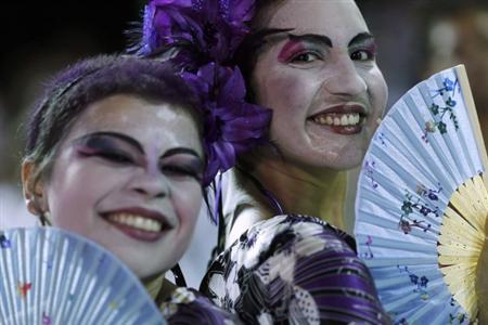 Revelers with paper fans smile at a masquerade party during Carnival celebrations in Salvador February 17, 2012. REUTERS/Ueslei Marcelino