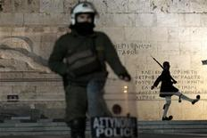 A policeman stands guard in front of a presidential guard during an anti-austerity rally in Athens February 18, 2012. Greece's cabinet tackled on Saturday how to implement austerity demanded by the EU and IMF as a 130-billion-euro ($171-billion) rescue seemed within reach, while the euro zone considered modifying a deal with private creditors to help Athens reduce its huge debts.  REUTERS/Yiorgos Karahalis
