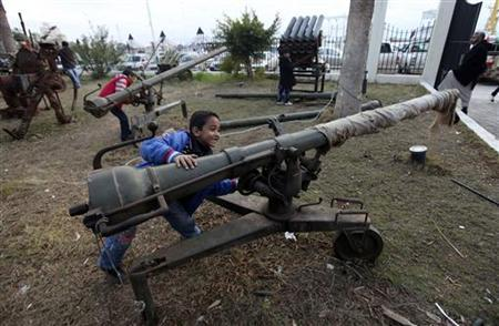 Children play with weapons used in the war against Muammar Gaddafi, during an exhibition held in conjunction with the Revolution of February 17 in Benghazi February 18, 2012. REUTERS/Esam Al-Fetori