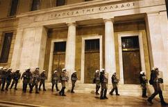 Riot policemen protect the building of the Bank of Greece during an anti-austerity protest in central Athens February 19, 2012. Several thousand Greeks demonstrated Sunday against punishing austerity measures to reduce the country's debt, on the eve of make-or-break talks in Brussels on a 130-billion-euro ($171 billion) bailout to avert bankruptcy.  REUTERS/Yiorgos Karahalis
