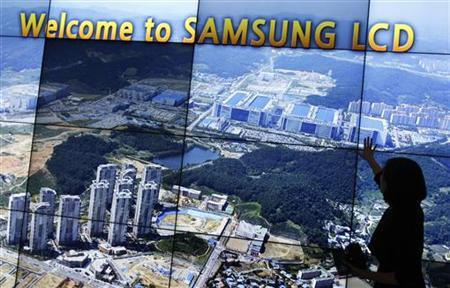 An employee of Samsung Electronics explains as a monitor shows the company's main factory at its showroom in Asan, south of Seoul, May 13, 2011.     REUTERS/Truth Leem