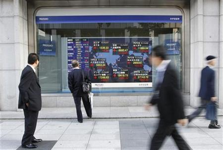 Passersby look at an electronic board displaying a rise in major market indices around the world, outside a brokerage in Tokyo October 27, 2011. REUTERS/Issei Kato/Files