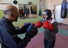 Sadaf Rahimi (R) trains inside a boxing club in Kabul February 13, 2012. In a country wrenched by decades of war, perhaps it is no surprise that three Afghan athletes going to the London summer Olympic, a taekwondo male duo including Beijing bronze medallist Rohullah Nikpai, and teenage female boxer Sadaf Rahimi, followed fighting sports.    REUTERS/Omar Sobhani