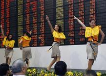 """Cebu Pacific airlines cabin crew perform a safety demonstration routine during a ceremony inside a trading floor of the stock exchange in Makati's financial district of Manila in this October 26, 2010 file photo. The Philippines, the perennial """"sick man of Asia"""", has rarely looked healthier and investors are placing their bets. Its stock market, the best performer in Asia last year, is up nearly 13 percent this year to a record high on Monday.  REUTERS/Romeo Ranoco/Files"""