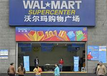 Employees stand in front of the gate to a Wal-Mart Supercenter in Chongqing municipality October 24, 2011. Wal-Mart stores in Chongqing reopened to surging crowds on Tuesday, two weeks after being shut down by local authorities for violating food and product standards. Picture taken October 24, 2011. REUTERS/Stringer