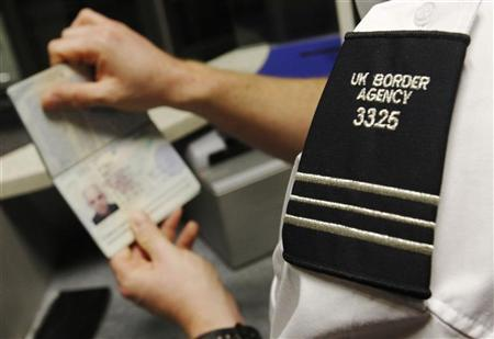 A UK Border Agency worker poses with a passport during a demonstration of the new facial recognition gates at the North Terminal of Gatwick Airport near London, November 23, 2009. REUTERS/Luke MacGregor