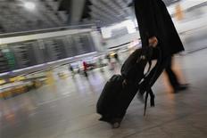 Человек проходит мимо табло вылетов в главном терминале аэропорта во Франкфурте-на-Майне 21 февраля 2012 года. Человек проходит мимо табло вылетов в главном терминале аэропорта во Франкфурте-на-Майне REUTERS/Alex Domanski