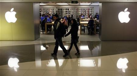 A couple walks past an Apple Store in downtown Shanghai February 18, 2012. REUTERS/Aly Song