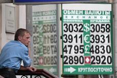 Мужчина стоит перед табло с курсами в валют в Москве, 13 августа 2010 года. Рубль стабилен в начале предпраздничный торгов среды, отыграв небольшим ростом при открытии дорогую нефть и незначительное укрепление пары евро/доллар. REUTERS/Alexander Natruskin