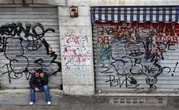 """Мужчина сидит перед закрытыми магазинами в Риме, 9 февраля 2011 года. Европейский долговой кризис будет основной темой переговоров представителей стран """"Большой двадцатки"""", которые состоятся на ближайших выходных, поскольку остальной мир ждет от еврозоны обещания укрепить ее систему антикризисной защиты. REUTERS/Max Rossi"""