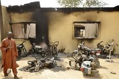 A man walks through the ruins of a zonal police headquarters after a bomb attack in Nigeria's northern city of Kano, January 21, 2012. REUTERS/Stringer