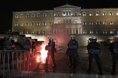 Police stand guard as a flare thrown by protesters burns on the ground in front of parliament during an anti-austerity demonstration in Athens February 22, 2012.     REUTERS/Yannis Behrakis