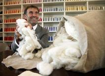Italian clothing designer Brunello Cucinelli holds raw cashmere wool in the Umbrian village of Solomeo October 7, 2009. REUTERS/Alessandro Bianchi