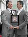 Vince McMahon (L), the chairman of World Wrestling Entertainment, Inc. holds a plaque as he poses with his son Shane after the former's Hollywood Walk of Fame star was unveiled in Hollywood, California March 14, 2008. REUTERS/Fred Prouser