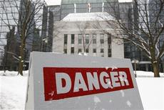 A sign warning pedestrians of falling ice from buildings above its path is seen in front of the Bank of Canada building in Ottawa January 17, 2012.       REUTERS/Chris Wattie