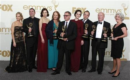 The cast and crew of ''Downton Abbey,'' winners for outstanding miniseries or movie, and outstanding writing for a miniseries, movie or a dramatic special, pose backstage at the 63rd Primetime Emmy Awards in Los Angeles September 18, 2011.  REUTERS/Lucy Nicholson
