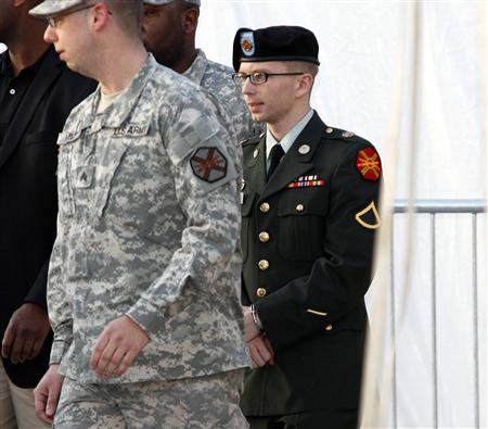 Army Pfc. Bradley Manning (R), in handcuffs, is escorted out of a courthouse in Fort Meade, Maryland February 23, 2012. Manning, a U.S. Army intelligence analyst accused of the largest leak of classified documents in U.S. history, deferred pleading guilty or not guilty in a military court arraignment on Thursday, marking the first step in a court martial that could land him imprisonment for life. REUTERS/Jose Luis Magana