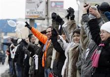 """Участники акции """"Большой белый круг"""" в Москве 26 февраля 2012 года. Тысячи человек вышли на улицы двух столиц в последние выходные перед голосованием за президента России, чтобы выразить протест против нечестных, по их мнению, выборов и фаворита кампании - Владимира Путина. REUTERS/Grigory Dukor"""
