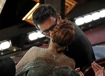 "French Director Michel Hazanavicius kisses his wife Berenice Bejo after winning the Oscar for best director for his film ""The Artist"" at the 84th Academy Awards in Hollywood, California, February 26, 2012.  REUTERS/Gary Hershorn"