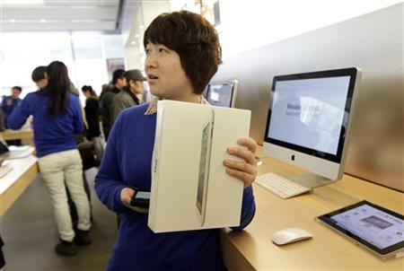 A salesgirl holding an Apple iPad 2 waits for a customer to pay in the company's flagship store in Beijing's Sanlitun Area, February 15, 2012. REUTERS/Jason Lee