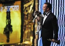 """Best actor winner Jean Dujardin of France carries Uggie the dog after """"The Artist"""" won the Oscar for Best Picture at the 84th Academy Awards in Hollywood, February 26, 2012.  REUTERS/Gary Hershorn"""
