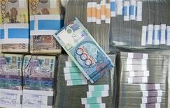 Банкноты валюты Казахстана тенге в отделении Казкоммерцбанка в Алма-Ате 4 февраля 2010 года. Казахстан понизил прогноз роста объема промышленного производства на 2012 год до 3,9 процента с прежних 6,4 процента в ожидании сокращения потребления нефти, металлов и зерна на фоне замедления темпов роста мировой экономики, сказал министр экономического развития и торговли Бакытжан Сагинтаев. REUTERS/Shamil Zhumatov