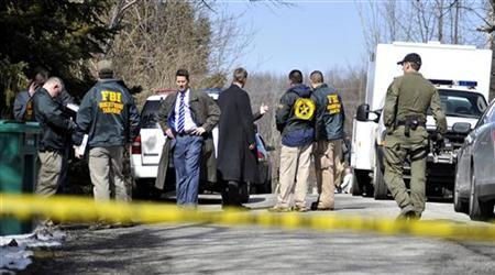 Federal agents stand outside the residence of suspected gunman T.J. Lane, who allegedly shot one girl and four boys inside Chardon High School in Chardon, Ohio February 27, 2012. REUTERS/Ron Kuntz