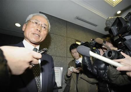 A lawyer for corporate pension fund manager AIJ Investment Advisors Co. speaks with reporters at the building housing the office of the company, after the Financial Services Agency ordered the company to suspend its business for one month earlier in the day, in this photo taken by Kyodo February 24, 2012. REUTERS/Kyodo