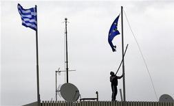 """Мужчина пытается снять испорченный флаг Евросоюза на здании Министерства иностранных дел Греции в Афинах, 8 февраля 2012 года. Европейский Центробанк сообщил во вторник, что приостанавливает прием греческих гособлигаций в качестве залога, добавив, что национальные центробанки могут использовать """"экстренное предоставление ликвидности"""" банкам. REUTERS/Yannis Behrakis"""
