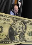 Шуточная долларовая купюра на бирже во Франкфурте-на-Майне, 24 октября 2008 года. Российский медиахолдинг СТС-Медиа в четвертом квартале 2011 года получил чистый убыток в $24,5 миллиона из-за обесценения активов на общую сумму $90 миллионов, сообщила компания во вторник. REUTERS/KaiPfaffenbach