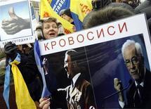 Украинцы выкрикивают лозунги, размахивая транспарантами на акции протеста в Киеве против налоговых новаций. 25 марта 2011.Авторитетные украинские экономисты предупредили премьер-министра Николая Азарова о рисках, которые сулит стране падение спроса на ее основную экспортную продукцию, металлы, и предложили оживить экономику с помощью госкредитов, попутно пополнив казну ростом налогов для состоятельных граждан. REUTERS/Gleb Garanich