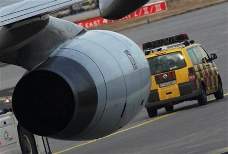An airport apron controller vehicle is pictured next to a Cathay Pacific Boeing B747-400 Aircract on the runway at Frankfurt's airport February 21, 2012. Strikes at Frankfurt airport, Germany's largest, will continue until the weekend, the GdF union, resulting in more flight cancellations and delays. Just under 200 apron control workers, such as those who guide aircraft to parking places, are striking over a pay dispute with Fraport, which runs the airport. REUTERS/Alex Domanski (GERMANY - Tags: BUSINESS TRANSPORT EMPLOYMENT)