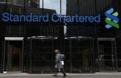 Женщина проходит мимо банка Standard Chartered в Лондоне, 13 октября 2010 года. Один из крупнейших банков Великобритании, Standard Chartered Plc, объявил в среду о росте доналоговой прибыли на 10,7 процента в 2011 году, показав положительную динамику ключевых финансовых показателей девятый год подряд благодаря бурно развивающейся азиатской экономике. REUTERS/Stefan Wermuth