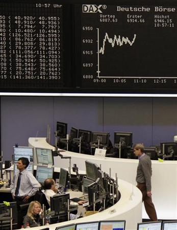 Traders are pictured at their desks in front of the DAX board at the Frankfurt stock exchange February 29, 2012.  REUTERS/Remote/Kirill Iordansky  (GERMANY - Tags: BUSINESS)