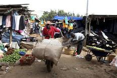 A man pushes a handcart through a market in the Kibera slum of the Kenyan capital Nairobi January 20, 2012.