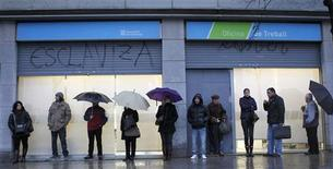 People wait for a government employment office to open in Barcelona February 2, 2012. REUTERS/Albert Gea