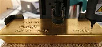 Нанесение гравировки на слиток золота на заводе Красцветмет в Красноярске 16 ноября 2009 года. Золотовалютные резервы России за неделю к 24 февраля увеличились на $5,2 миллиарда, в основном, из-за положительной переоценки евро и золота, а также благодаря покупкам валюты российским Центробанком в ходе интервенций на внутреннем валютном рынке. REUTERS/Ilya Naymushin
