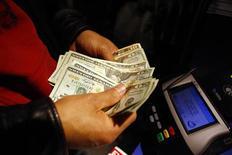 Покупатель считает деньги в магазине в Нью-Йорке, 24 ноября 2011 года. Вероятность резкого мирового замедления снизилась благодаря политическим мерам, недавно принятым в еврозоне и направленным на борьбу с долговым кризисом, сообщил в четверг Международный валютный фонд, предупредив, однако, что риски для мирового роста сохраняются. REUTERS/Eric Thayer