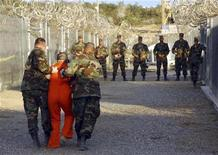 Архивное фото военной полиции США, чьи сотрудники сопровождают задержанного в его камеру на военной базе в заливе Гуантанамо 1 мая 2011.Американские парламентарии и пресса раскритиковали проект командующего тюрьмой на базе ВМФ в Гуантанамо Дэвида Вудса, распорядившегося потратить $744.000 из казны на футбольное поле для заключенных. REUTERS/Stringer/Files