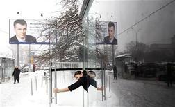 Женщина открывает дверя рядом с билбордом с портретом кандидата в президенты России Михаила Прохорова в Москве 16 февраля 2012. Суббота и воскресный день президентских выборов обещают российской столице облачность с температурой воздуха в светлое время суток около минус 1-2 градусов, ожидают синоптики. REUTERS/Mikhail Voskresensky