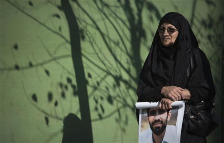 A woman holds a poster of Iranian nuclear scientist Mostafa Ahmadi-Roshan, who was killed in a bomb blast in Tehran on January 11, before his funeral after Friday prayers in Tehran January 13, 2012. REUTERS/Morteza Nikoubazl