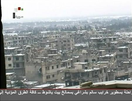 Damaged buildings covered in snow are seen in Baba Amro district of Homs in this still image taken from video footage broadcast on Syria TV on  March 2, 2012. A REUTERS/Syria TV via Reuters TV