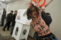 Полиция задерживает украинских активисток Femen на избирательном участке в Москве, 4 марта 2012 года. Известные эпатажным поведением украинские феминистки устроили протестную топлесс-акцию на избирательном участке в центре Москвы, где несколькими минутами ранее проголосовал кандидат в президенты Владимир Путин. Reuters/Denis Sinyakov (RUSSIA  - Tags: POLITICS ELECTIONS) TEMPLATE OUT.