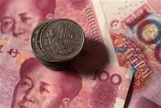Монеты в один юань лежат на банкнотах в 100 юаней в Пекине, 11 августа 2011 г. Центробанк Китая расширит торговый диапазон юаня, сообщил в понедельник глава банка Чжоу Сяочуань в интервью новостному агентству Синьхуа. REUTERS/Petar Kujundzic