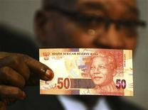 South Africa's President Jacob Zuma holds up a banknote bearing the face of former president Nelson Mandela in Pretoria February 11, 2012. REUTERS/Stringer